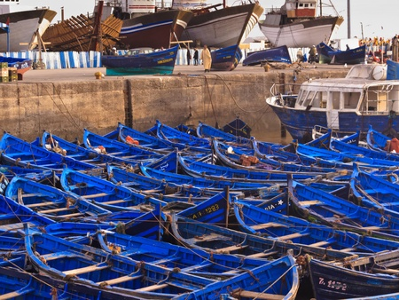 moorings: ESSAOUIRA, MOROCCO - JANUARY 13, 2010: Group of blue fishing boats tied together in harbor on January 13, 2010 Essaouira, Morocco.