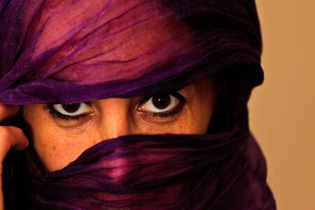 ESSAOUIRA, MOROCCO - JANUARY 16, 2010: Closeup of an unidentified Moroccan woman with a purple veil or burka over her face on January 16, 2010 in Essaouira, Morocco