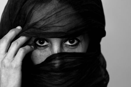headress: ESSAOUIRA,MOROCCO - JANUARY 16, 2010. Black and white closeup of an unidentified Moroccan woman with a veil over her face on  January 16, 2010 in Essaouira, Morocco Editorial
