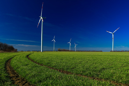 windmills at work with a green field and dark blue sky representing clean source of energy
