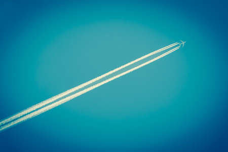 Airplane with diagonal trails of fumes in a dark blue sky photo