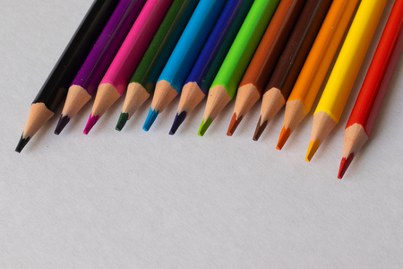 Colored pencils semicircle lie on the table on a white background.