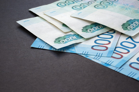 Russian banknotes scattered on the table in the upper corner. Black background.