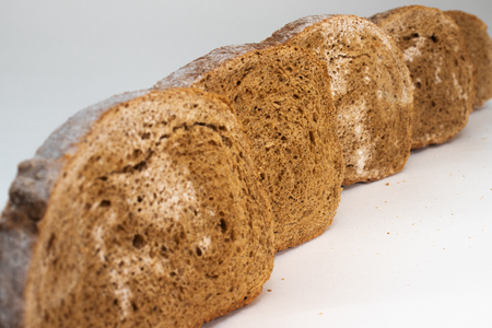 Several slices of rye bread covered with mold are located on the table one after another. Photo at an angle on a white background.