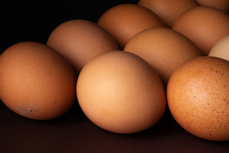 On the table, in three rows, are chicken eggs. These are rustic, natural eggs. The background is two-tone brown and black.