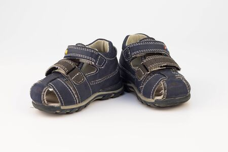 On a white background - old childrens sandals with Velcro for a boy. Sandals are gray-blue and trimmed with white thread.