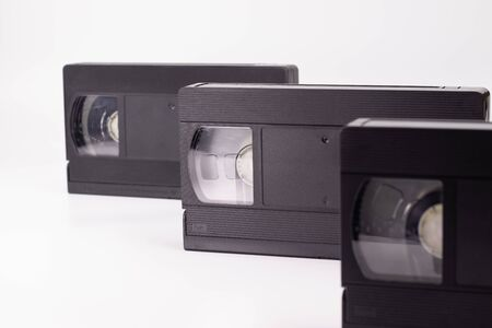 Three old black video cassettes stand in a row one after another on a white background. 版權商用圖片