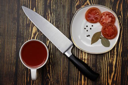 On a wooden table is a saucer with chopped tomato, peppercorns and bay leaf, a cup with tomato juice. In the middle lies a knife with a black handle. Stock Photo