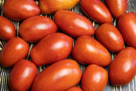 On a wooden table are red tomatoes. Stock Photo