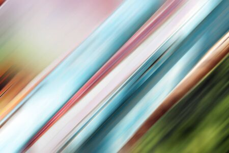 Abstract background of blue, pink, brown and green colors blurred at an angle of 45 degrees.