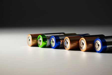 On a gray-white background lie in a row of lithium batteries. Battery colors are blue, orange and green.