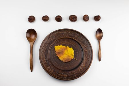 On a white background is a plate of clay. It contains a yellow autumn leaf. Nearby are two wooden spoons. On top are six chestnuts in a row. Stock Photo