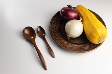 On a white background in a clay plate two heads of onions and zucchini, next to two wooden spoons. Stock Photo - 131736042