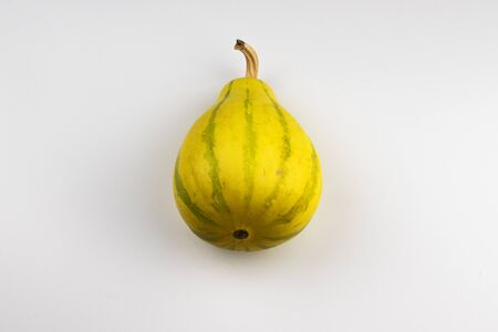 Yellow, decorative pumpkin on a white background.Pumpkin is located in the center of the photo.