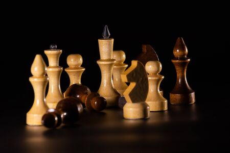 On a black background are chess pieces illuminated by a side light. Chess pieces brown and ivory. Stock Photo