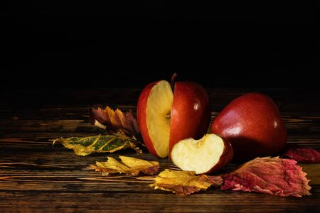 Two ripe, red apples lie on a wooden table, one apple is sliced. On the table are autumn yellow leaves.
