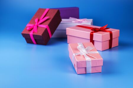 Four multi-colored gift boxes with ribbons on a blue background.