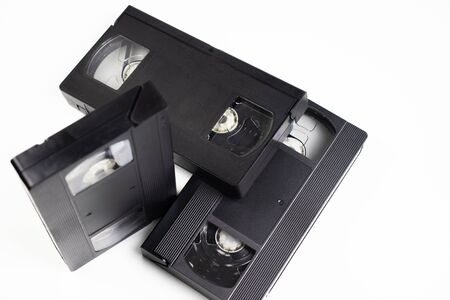 Three videotapes are on a table with a white background. One video cassette stands upright.