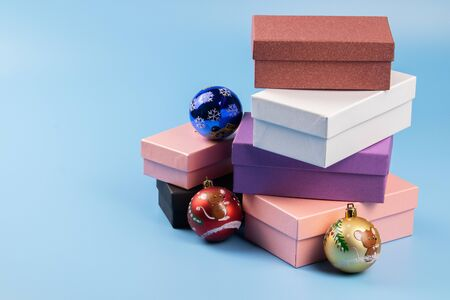 Six multi-colored gift boxes stand in a box on a blue background. On the boxes are Christmas balls.