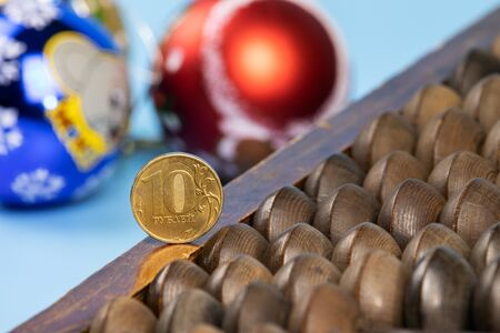 Abacus with iron rubles on a blue background. In the background are Christmas balls. Stock Photo