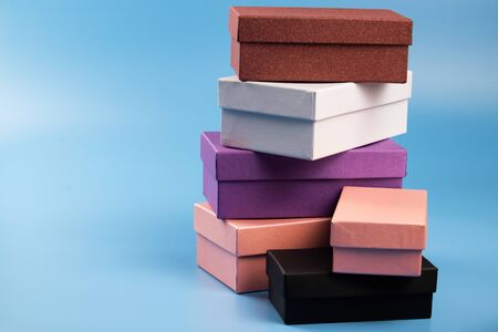 Six multi-colored gift boxes stand on a stack on a blue background. Stock Photo