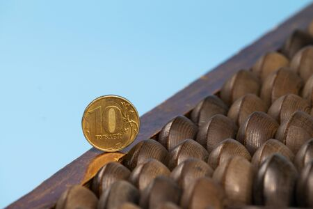 Abacus with iron rubles on a blue background.