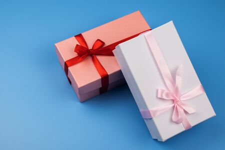 Two multi-colored gift boxes with ribbons on a blue background.