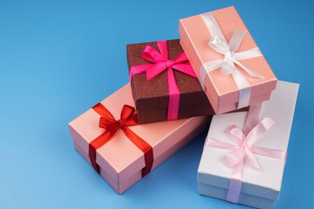 Four multi-colored gift boxes tied with ribbons on a blue background. Stock Photo