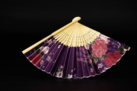 On a black background lies a colored folding fan. The color is lilac with red and white roses.