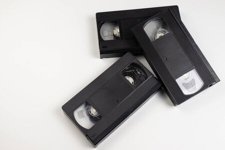 Old videotapes are randomly scattered on a white background.