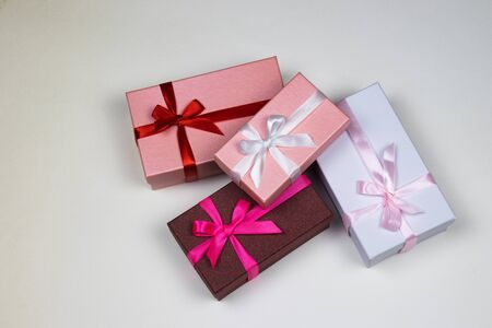 Four multi-colored gift boxes with ribbons on a white background. Stock Photo