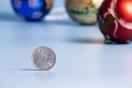 Five iron rubles in the foreground. In the background are three Christmas balls on a blue background.