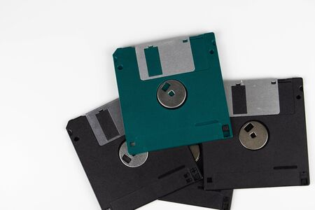 Four old floppy disks in a heap lie on a table with a white background. The color of one diskette is green.