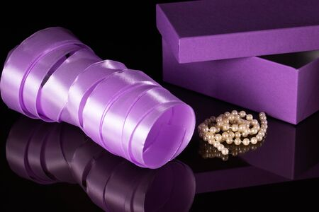 On a black glass table is a lilac gift box with a ribbon and mother of pearl beads. Stock Photo
