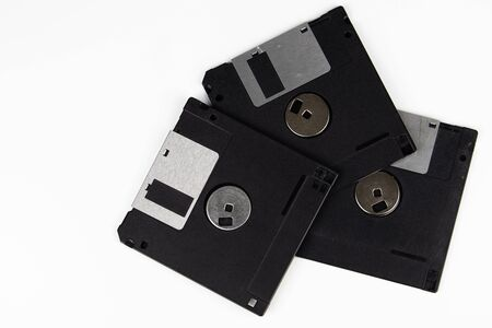 Three old floppy disks are lying on top of each other on a table with a white background. The color of the floppy disks is black.