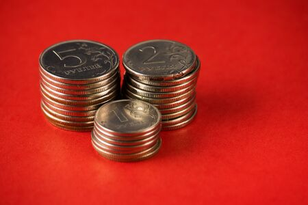 On a red background are three columns of ruble coins in denominations of five, two and one ruble.