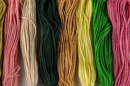 Sieben Stränge farbiger Garne zum Sticken liegen hintereinander auf einem Tisch. Sie sind vertikal angeordnet. Die Farben sind rosa, grün, gelb und ihre Schattierungen. Foto-Nahaufnahme.