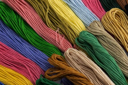 At an angle of forty-five degrees in the photo there are threads for embroidery in two rows. They have various color shades of blue, green, red and other colors. Close-up photo.