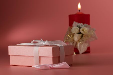 In the foreground of the photo taken at a slight angle is a box and a pink bow. In the background is a burning red candle tied with bows. The background is highlighted. The background of the photograph is pink. Banque d'images - 138466061