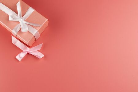 In the upper right part of the photo is a pink box and a bow lying next to it. The box is tied with a ribbon. The background of the photograph is pink. The photograph is taken from above. Foto de archivo - 138466007