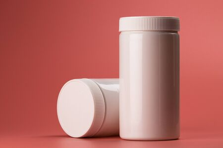 The photo shows two empty white containers of white color. One container lies on its side next to another. Background is pink. Banco de Imagens