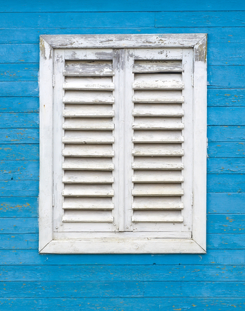 jalousie: Old white window with wooden shutters on the blue wall of boards.