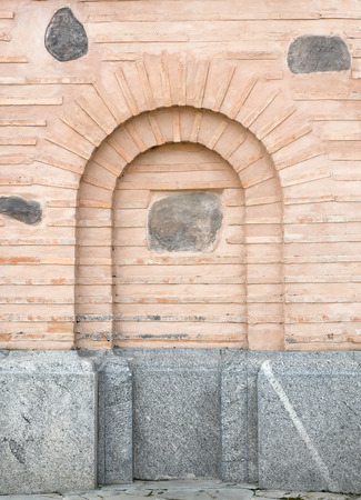 substructure: Old church brick wall with a granite foundation and arch imitation.