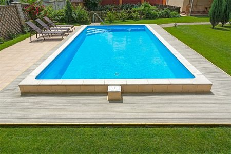 private access: Swimming pool in the yard of a private house with a seating area and garden furniture.