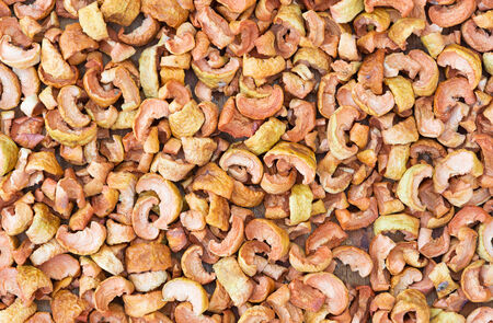 substrate: Background of dried apple slices on a wooden substrate.
