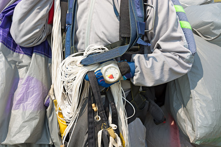 altimeter: Skydiver after landing. Holding a chute opening. On hand altimeter. Close-up.
