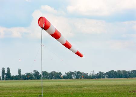 Windsock against cloudy sky. Airfield with green grass.
