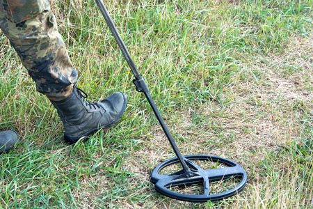 Search for treasure with metal detectors at the autumn meadow. Foot hunter and a fragment of the instrument close-up.