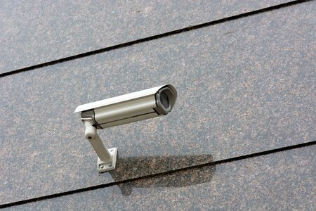 Surveillance Camera mounted on a granite wall. photo