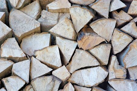 Background of stacked firewood close up. Chopped wood.